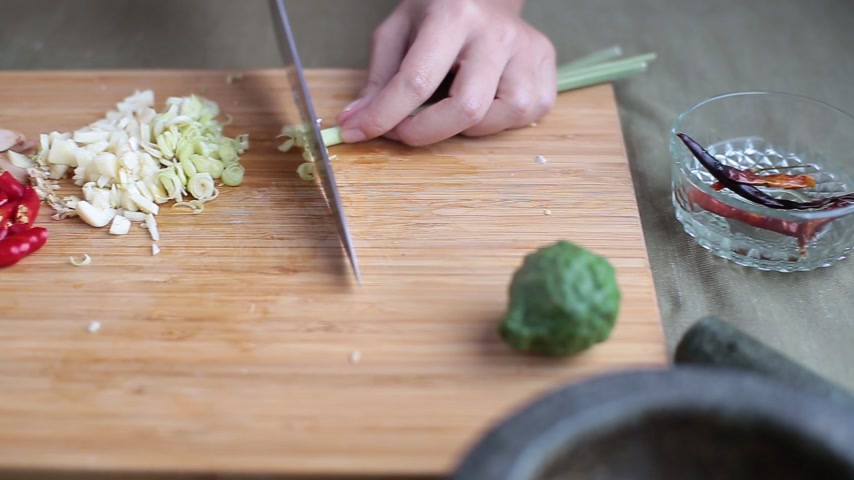 Female hand slicing lemongrass with chef knife on bamboo wooden chopping block with other Thai herbs beside for making Thai red curry or Panang recipe. Vídeos