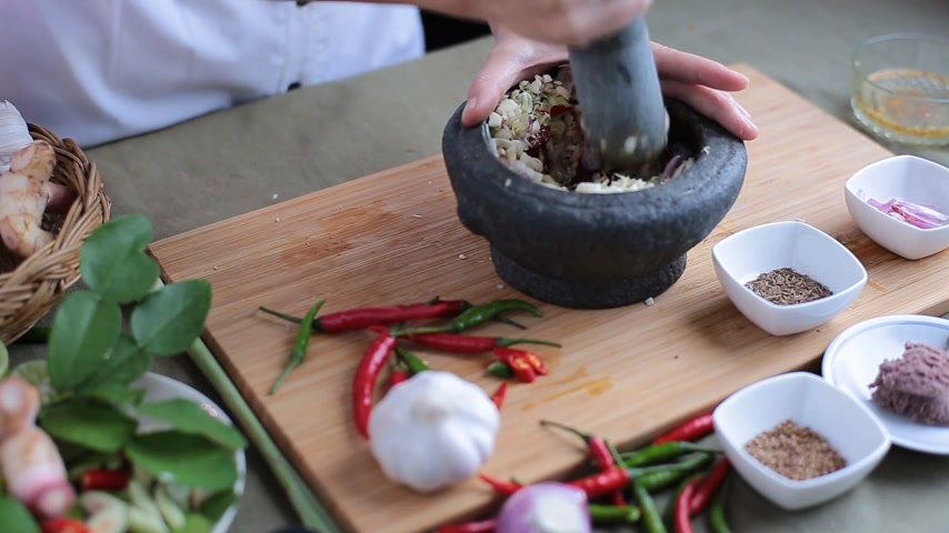 chalota : A female hand pounding many kinds of herbs in mortar to make Thai red curry chili paste or Panang. Stock Footage