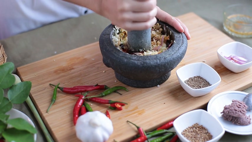 kari : A female hand pounding many kinds of herbs and add some caraway and coriander seed in mortar to make Thai red curry chili paste or Panang.
