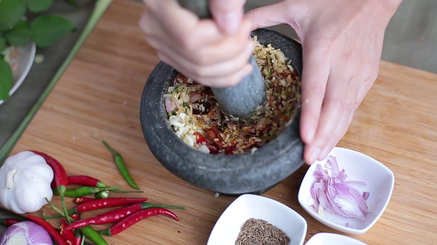 kari : A female hand pounding many kinds of herbs in mortar to make Thai red curry chili paste or Panang. Dostupné videozáznamy