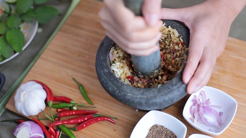 soğancık : A female hand pounding many kinds of herbs in mortar to make Thai red curry chili paste or Panang. Stok Video