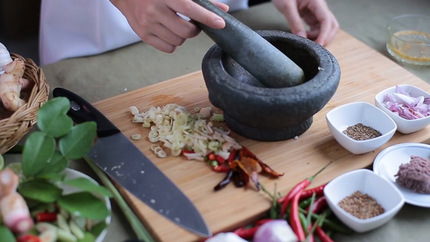 soğancık : A female hand put many kinds of Thai herbs in mortar and pulverize to make Thai red curry chili paste or Panang.