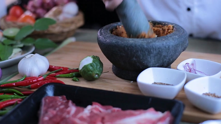 shallot : A female hand pounding many kinds of herbs in mortar to make Thai red curry chili paste or Panang. Stock Footage