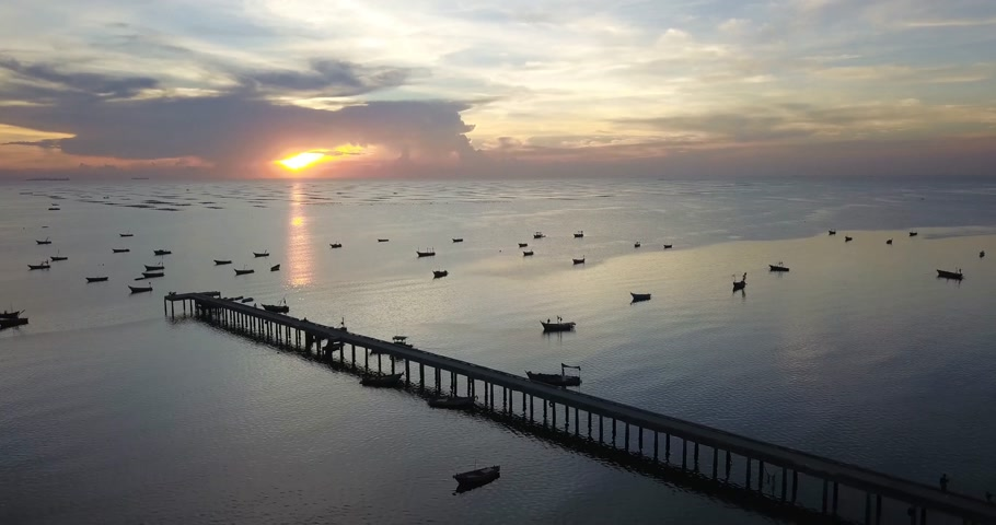 Aerial view of jetty bridge traveling around the sea with beautiful sunset showing boats on water surface, drone shot, videography. Vídeos