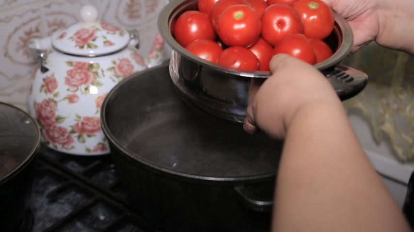blanching : tomatoes in a pot of boiling water