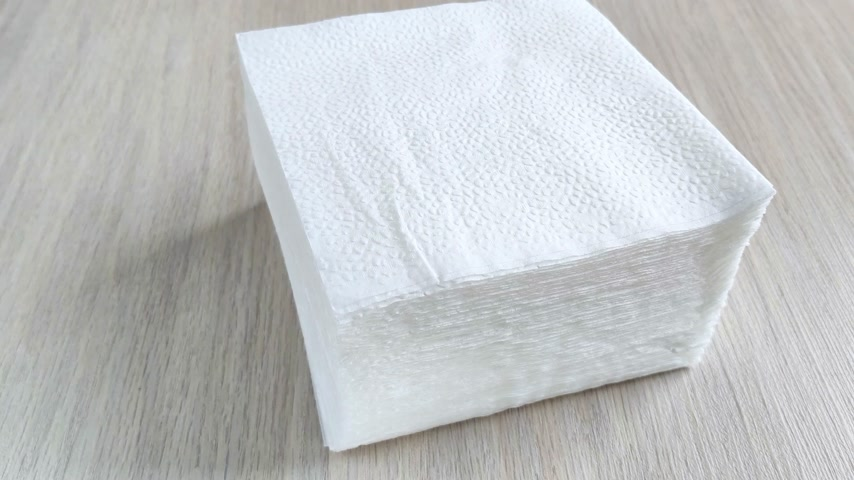 masa örtüsü : Stack of white square napkins on wooden table. Female hand takes one paper towel from above with fingers. Close-up, daylight