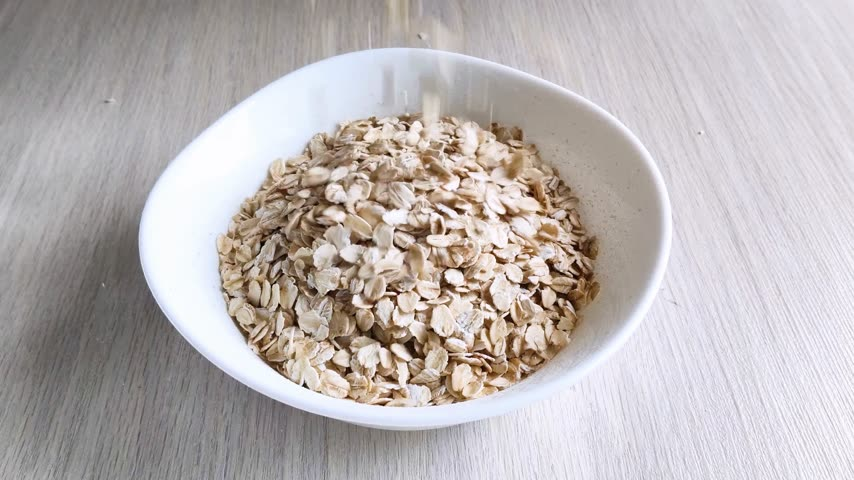 окропляет : Dry oatmeal is poured into white bowl. Cooking healthy nutritious breakfast. Close-up, daylight