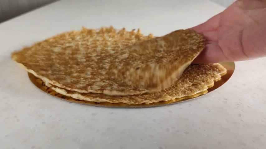 ruddy : Thin pancakes on marble table. Female hand quickly puts one pancake on other. Close-up. Fried ruddy national Russian food for breakfast and Shrovetide