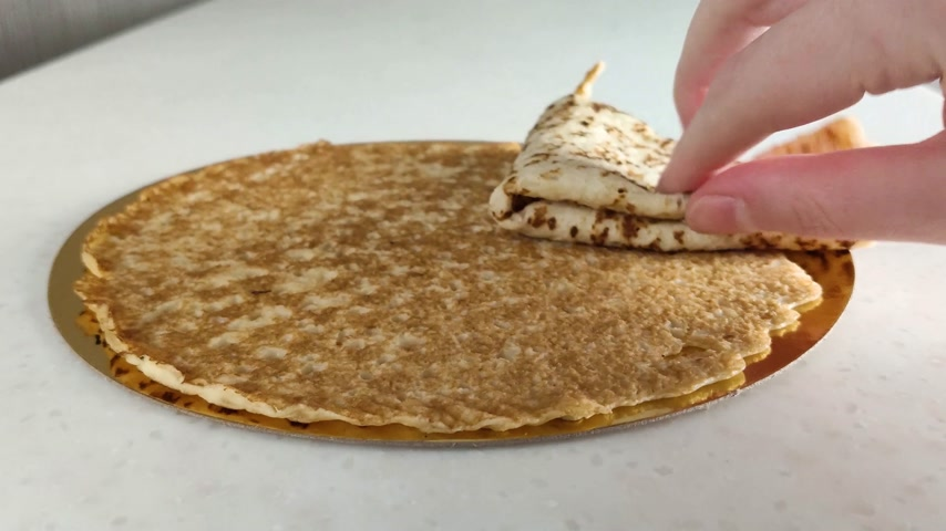 ruddy : Thin pancakes on marble table. Female hand folds one pancake into triangle and takes it. Close-up. Fried ruddy national Russian food for breakfast and Shrovetide