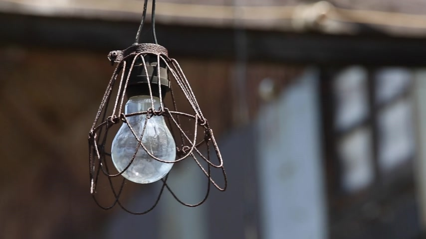 rustik : old light bulb in abandoned barn on the wind