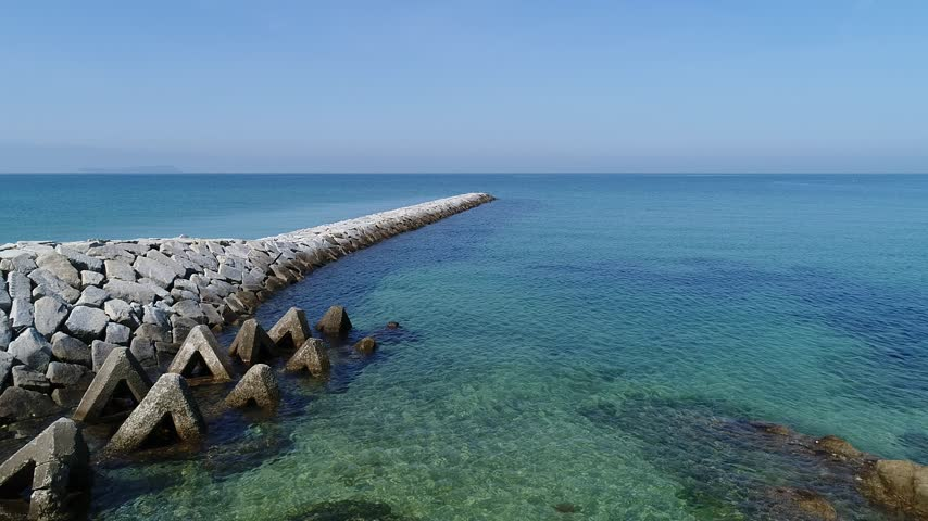avançar : Aerial view from advance flying drone, breakwater of stone in the sea