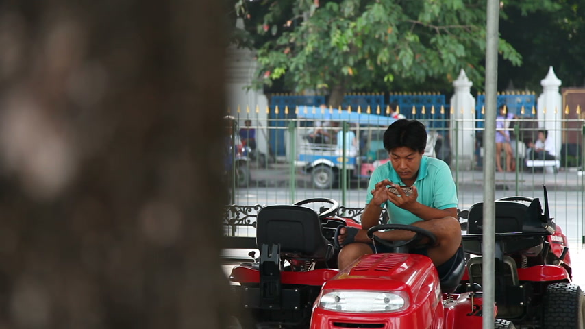 usual : BANGKOK, THAILAND - Usual street life in Bangkok. Driver sits on bike and swipes finger across the smartphones screen.