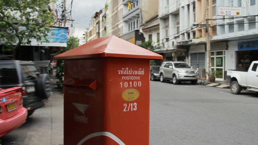 usual : BANGKOK, THAILAND - October 24, 2012. Usual streetlife. Moving transport, walking people. Bright red post box for letters and postcards.