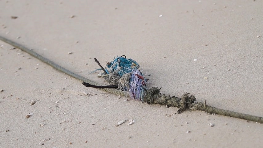 threadbare : Old rope made of different colorful parts and threads lies on sand. Rawai beach, Phuket island, Thailand.