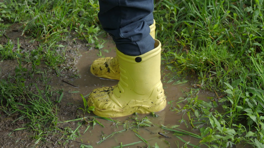 bochechudo : Little child in bright yellow rubber boots splashing in a puddle. Kids feet protected from dirty water.