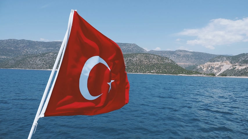 ensign : Flag of Turkey waving in the wind against Mediterranean sea in sunny day.