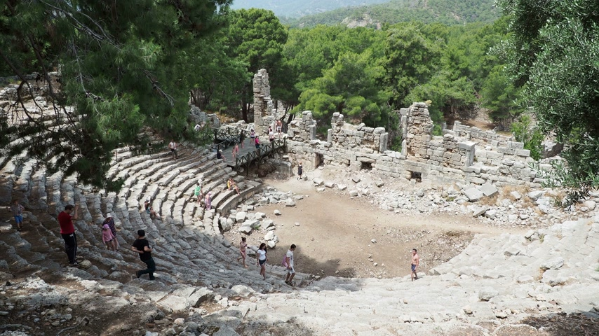 phaselis : PHASELIS, TURKEY - May 19, 2018. Tourists walking on ruins of amphitheatre of ancient Phaselis city. Stock Footage