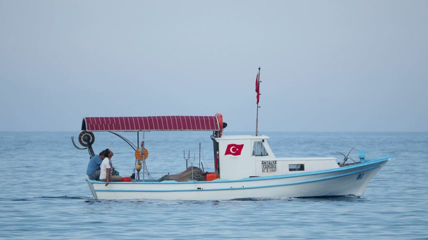 zakázáno : KEMER, TURKEY - May 12, 2018. Men talking in moving motor boat. Vehicle sails on the sea past the buoys.