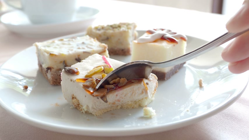 souffle : White plate full of different pastries. Tasty desserts with topping, coconut flakes. Somebody cutting a pastry with a spoon. Stock Footage