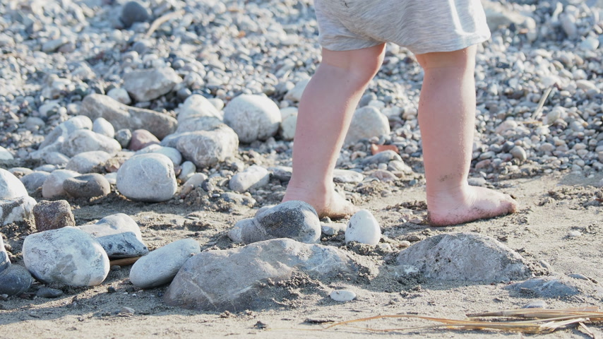 bare foot : Baby playing with stones on beach. Kids hands full with sand. Outdoor games.