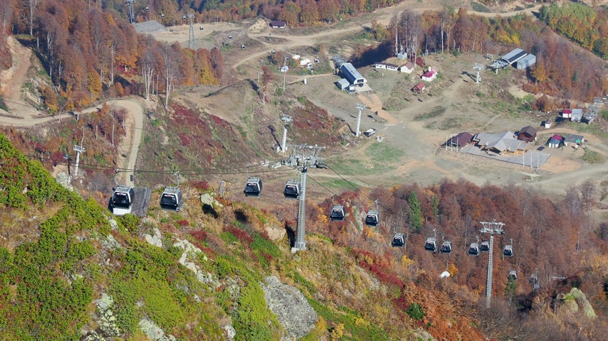 krasnodar region : Moving cabins of the cable road. Funicular with words Rosa Khutor on cabins. Russia. Stock Footage