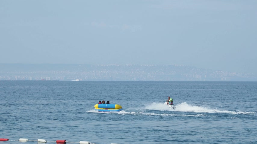 jet ski : KEMER, TURKEY - May 12, Tourists have fun in the water attraction - inflatable sofa that moves with jet ski.