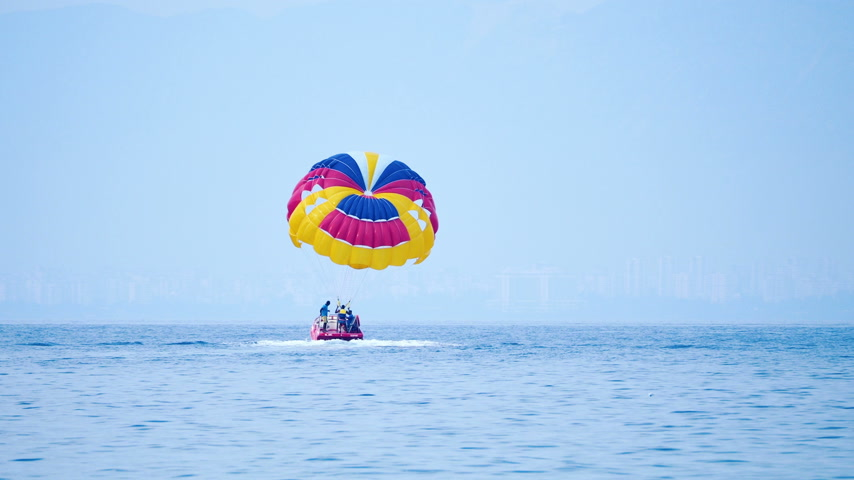 uçurtma : KEMER, TURKEY - May 12, Tourists have fun in the water attraction - parasailing. Man with parachute moves with motor boat.
