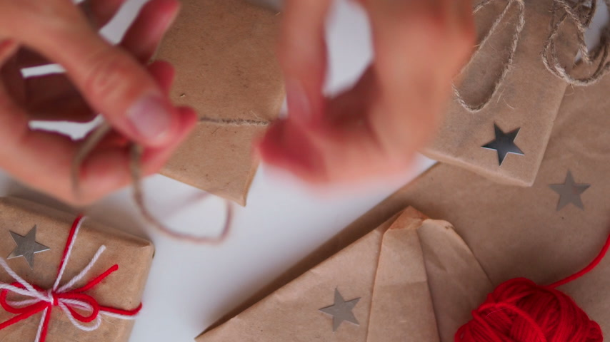 скрепки : Woman is wrapping present box with craft paper and red paper clip. Christmas and New Year background with DIY girts.