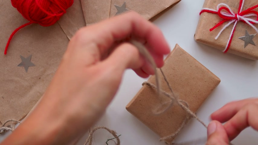 bağlayıcı : Woman is wrapping present box with craft paper and red paper clip. Christmas and New Year background with DIY girts.