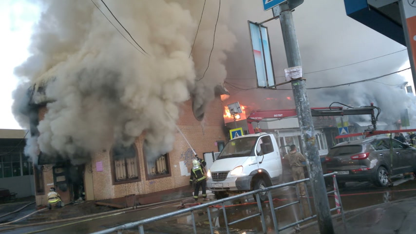 firemen : ODINTSOVO, RUSSIA - May 23, 2017. Large fire in a shopping centre near railway station. Stores are burning in the illegally constructed building.