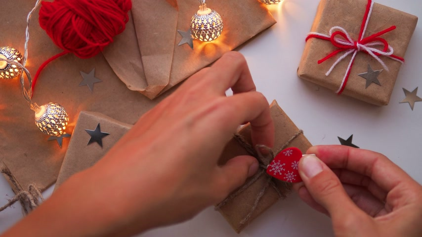 karácsonyi ajándék : Woman is wrapping present box with craft paper and red paper clip. Christmas and New Year background with DIY girts.