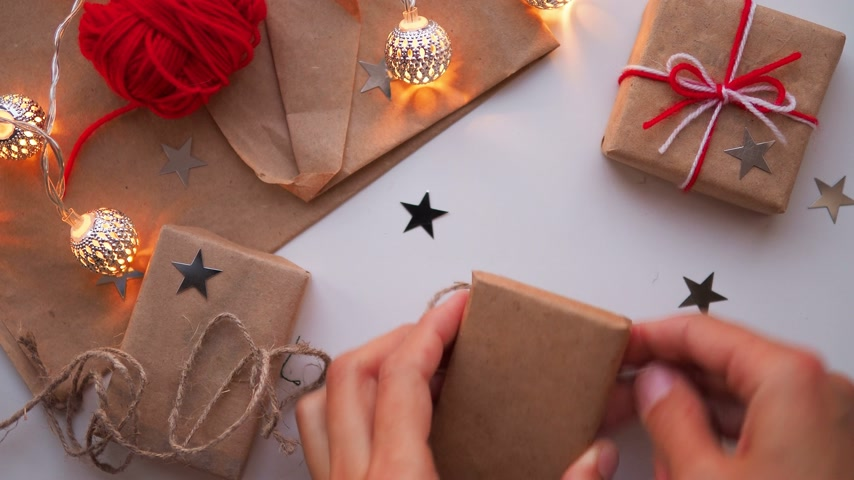 kötés : Woman is wrapping present box with craft paper and red paper clip. Christmas and New Year background with DIY girts.