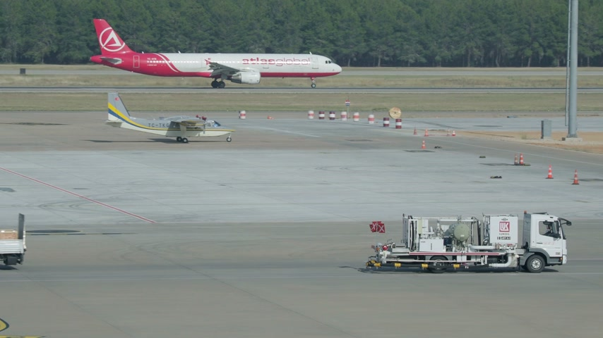 metin alanı : ANTALYA, TURKEY - May 22, 2018. Gasoline tank truck Lukoil moving on the takeoff field of the airport. Airplane takes off from the ground on the takeoff field. Stok Video
