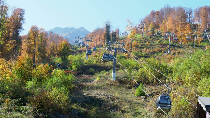 funicular : ROSA-KHUTOR, RUSSIA - October 13, 2018. Moving cabins of the cable road. Funicular moving over trees on mountains slopes. Stock Footage