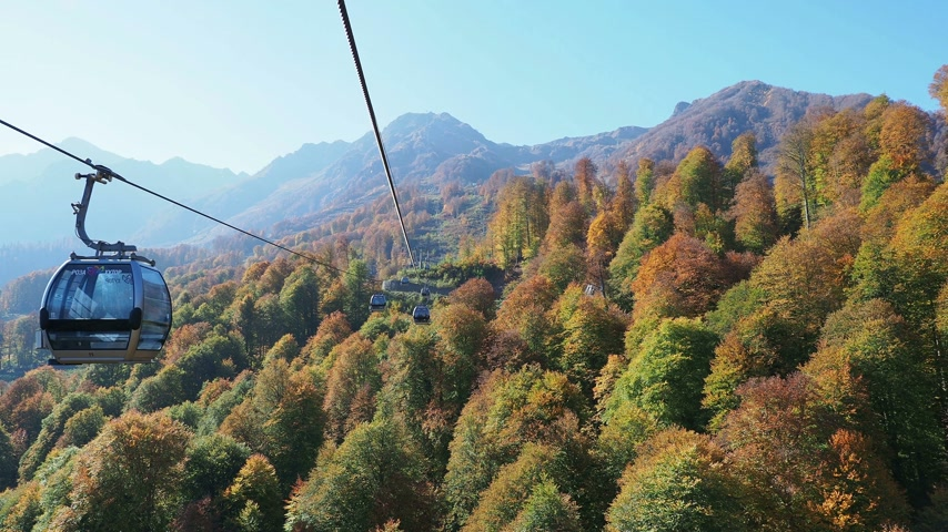 fülke : ROSA-KHUTOR, RUSSIA - October 13, 2018. Moving cabins of the cable road. Funicular moving over trees on mountains slopes. Stock mozgókép