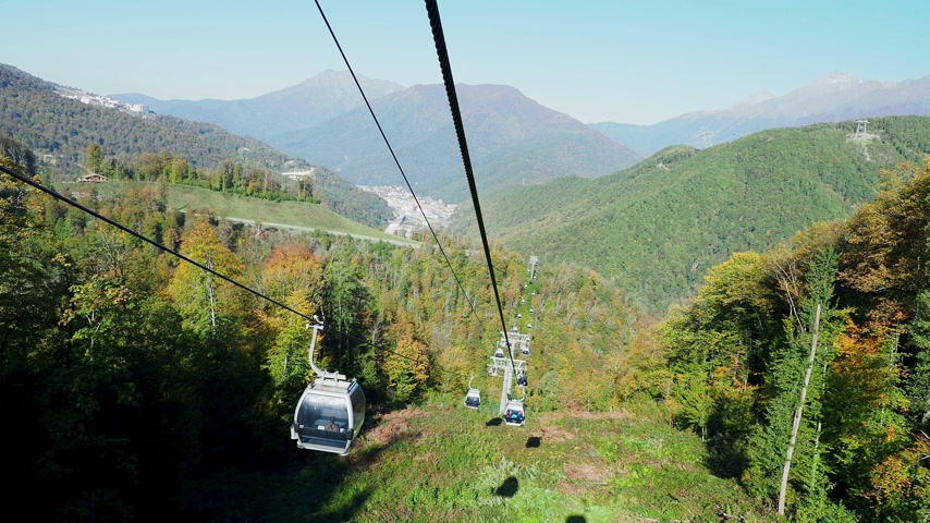 sochi : ROSA-KHUTOR, RUSSIA - October 13, 2018. Moving cabins of the cable road. Funicular moving over trees on mountains slopes. Stock Footage