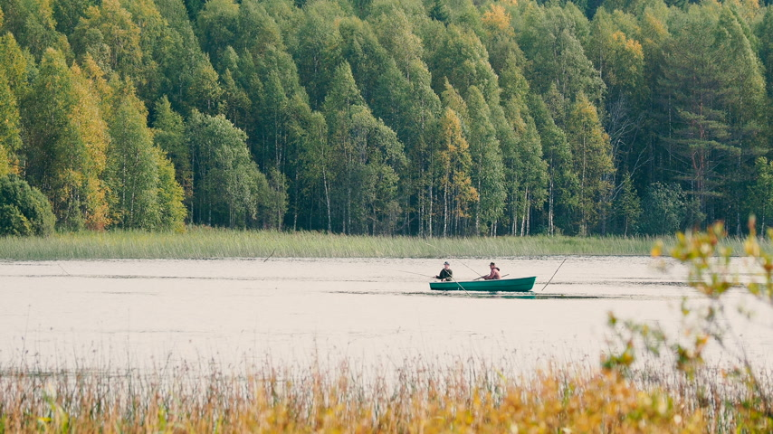 national park : Two man fishing on boat. Kenozerskiy national park, Russia.