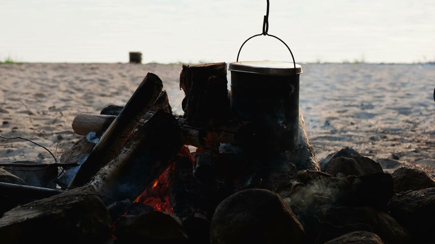 vapor : Cooking soup on a fire pot. Summer camping on beach. Kenozero national park, Russia.
