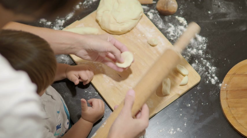 rolling pin : Cooking with children. Mother and son are making dumplings.