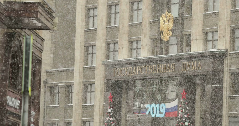 hanedan arması : State Duma. Entrance of building decorated for New Year 2019 celebration. Snowfall. Moscow, Russia. Stok Video