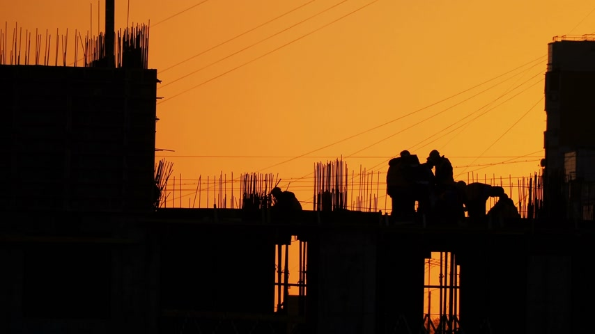neúplný : Construction of residential building. Builders go on the unfinished floor with protruding fittings. Silhouettes of workers on the background of an orange sunset. Dostupné videozáznamy
