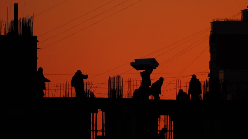 unfinished : Construction of residential building. Builders go on the unfinished floor with protruding fittings. Silhouettes of workers on the background of an orange sunset. Stock Footage