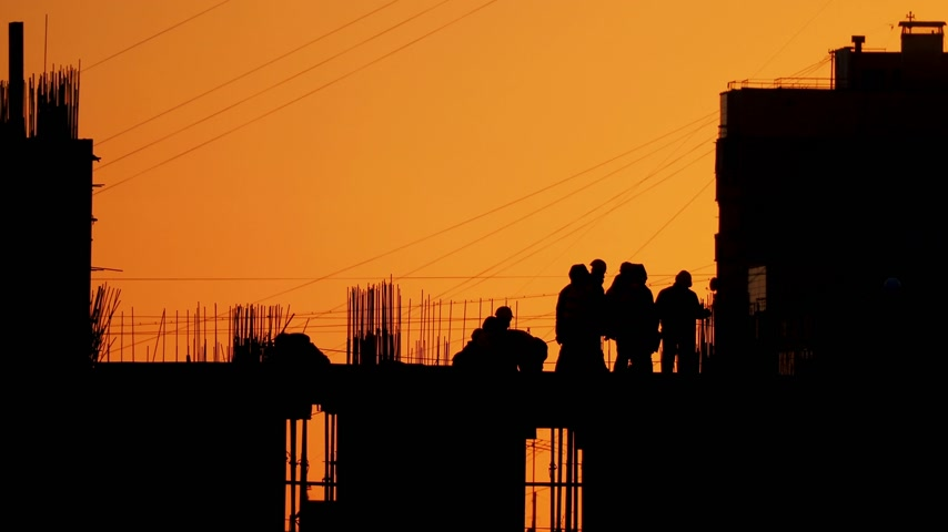robotnicy : Construction of residential building. Builders go on the unfinished floor with protruding fittings. Silhouettes of workers on the background of an orange sunset. Wideo