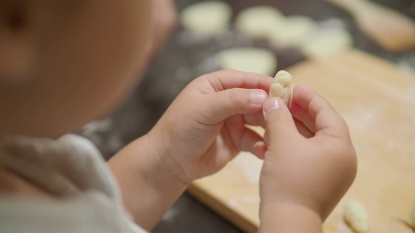 штифт : Cooking with children. Mother and son are making dumplings.