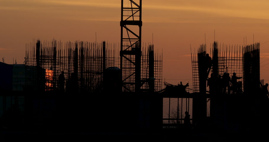 lakó : Construction of residential building. Builders go on the unfinished floor with protruding fittings. Silhouettes of workers on the background of an orange sunset. Stock mozgókép
