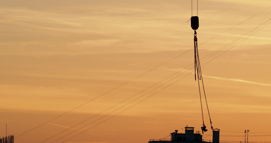 арматура : Construction crane with chains on the background of an orange sunset.