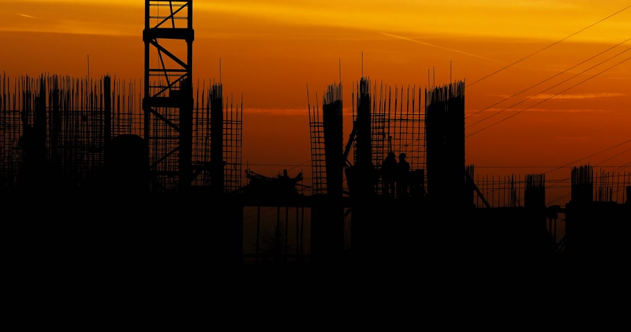 арматура : Construction of residential building. Builders go on the unfinished floor with protruding fittings. Silhouettes of workers on the background of an orange sunset. Стоковые видеозаписи