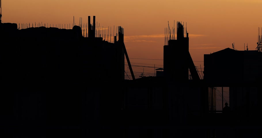 incompleto : Construction of residential building. Builders go on the unfinished floor with protruding fittings. Silhouettes of workers on the background of an orange sunset. Stock Footage