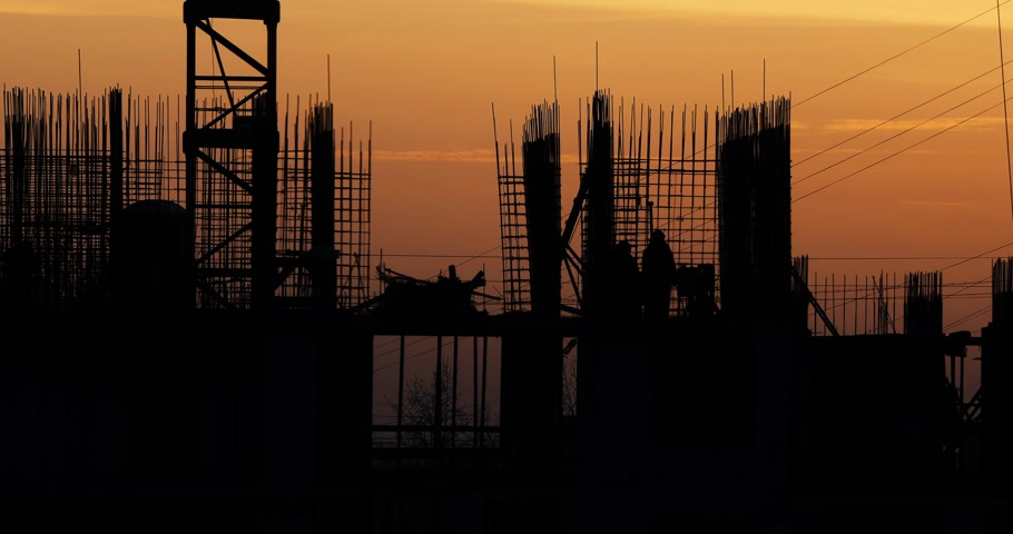 inacabado : Construction of residential building. Builders go on the unfinished floor with protruding fittings. Silhouettes of workers on the background of an orange sunset. Stock Footage