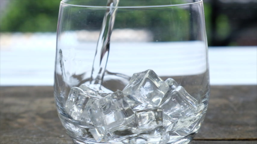 clear the table : Pouring plain water in a glass with ice cubes. Slow motion.